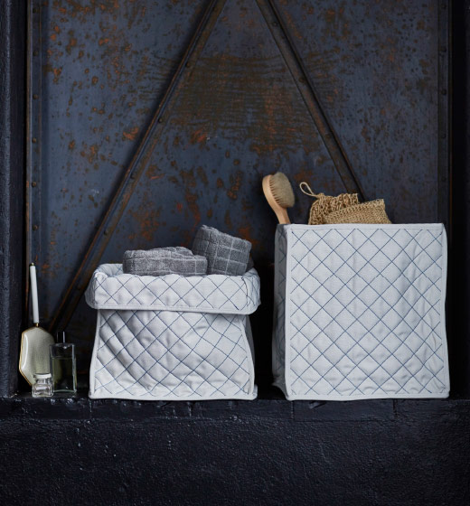 Two grey textile baskets, one with towels and the other with shower accessories.
