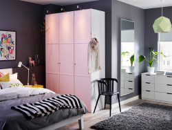 A large bedroom with a white wardrobe with light pink doors combined with a bed and chest of drawers, both in white.