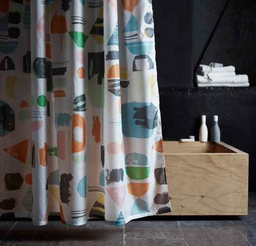 A shower curtain with pattern of paint brush strokes and paper clipings in pastel colours.