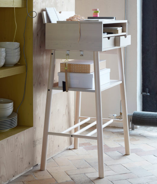 A standing desk in solid wood with space for laptop, chargers, calendars, mail and keys.