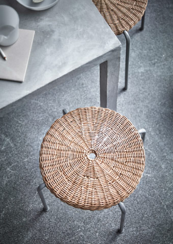 A rattan stool with grey steel legs, seen from above.