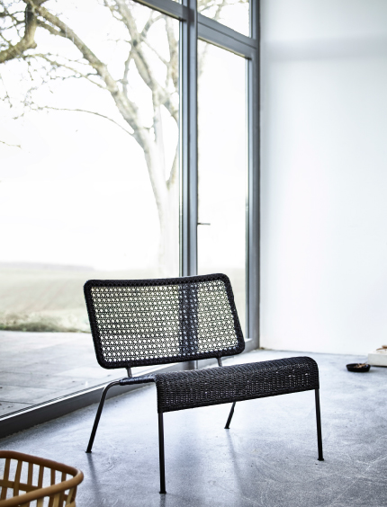 A black easy chair made of woven paper cords that looks lika bamboo and steel.