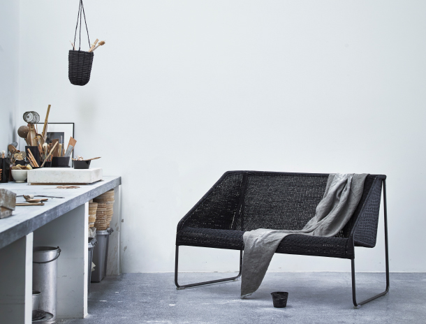 A small black sofa made of woven paper cords that looks lika bamboo and steel.