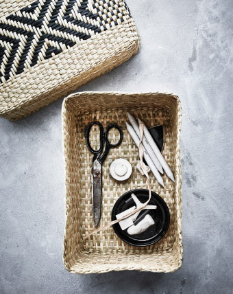 A handwoven basket in seagrass filled with pencils and a pair of scissors.