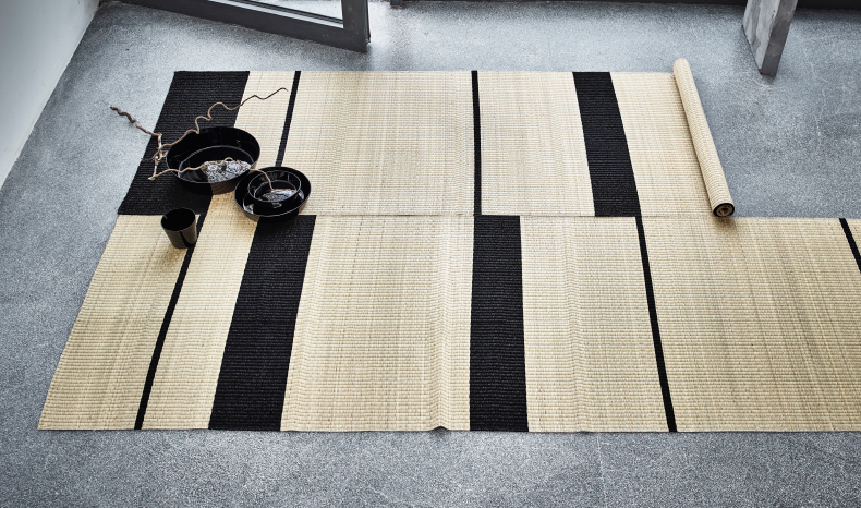 Two seagrass rugs with black stripes.