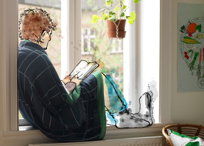 A man sitting in a window bay with a black throw around his shoulders, reading a book.