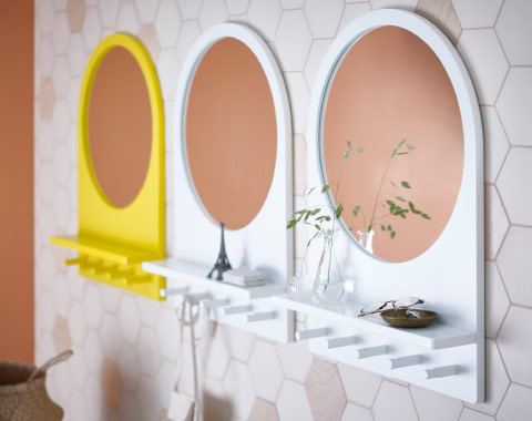 A wall with three mirrors in a row, one yellow and two white. Each mirror has a small shelf and five hooks.