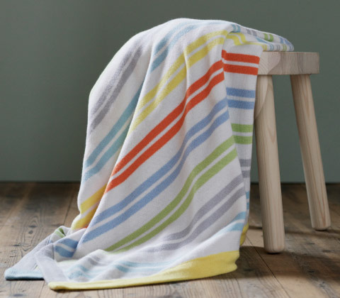 A striped blanket in orange, yellow, light blue and gray.