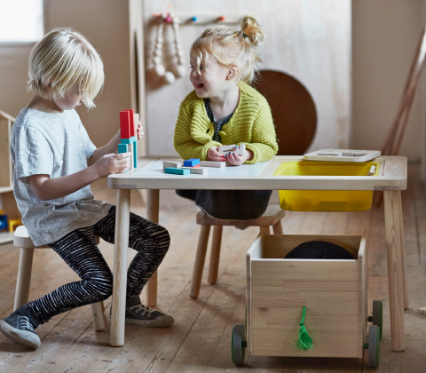 Two children sitting by a children's table, playing with wooden blocks.