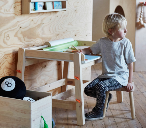 A boy sitting by a children's desk that can be both tilted and adjusted to three different heights.