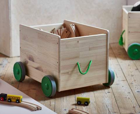 A wooden crate on wheels filled with a wooden train set.