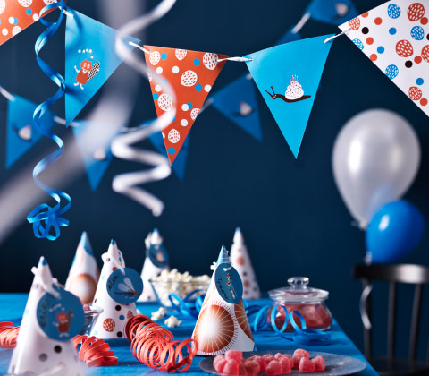 A birthday party with a table, set with colorful paper hats, streamers and garlands.