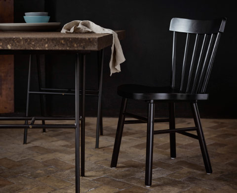 A black dining chair in solid wood.