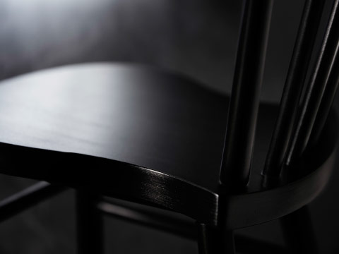 A close-up of a black dining chair in solid wood.