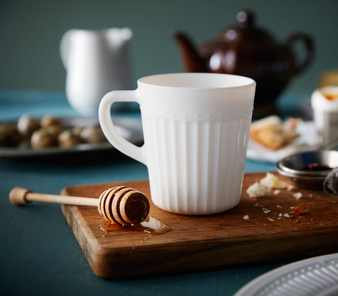 A mug in white tempered glass with a honey dipper shown on a small chopping board.
