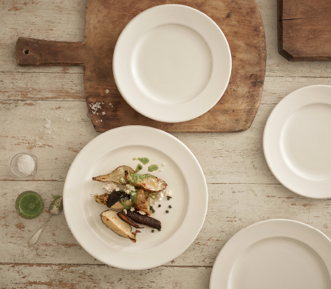 Several off-white plates in stoneware, one with roasted root vegetables.