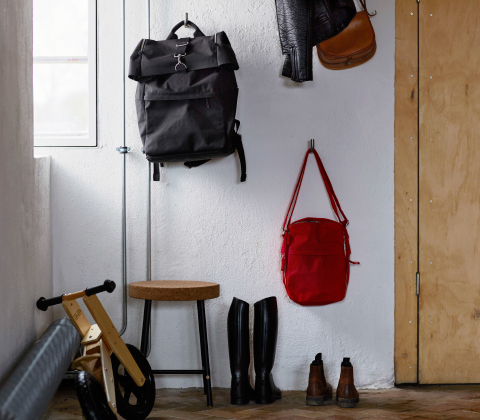 A black backpack hanging on the wall in the hallway.