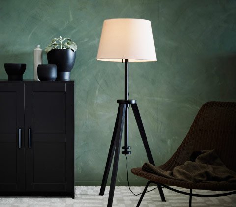 A black height adjustable floor lamp base in the shape of a camera stand combined with a white shade.