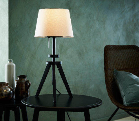 A black table lamp base in the shape of a camera stand combined with a white shade.