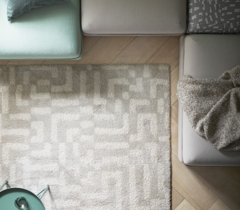 A square rug with an off-white geometric pattern.