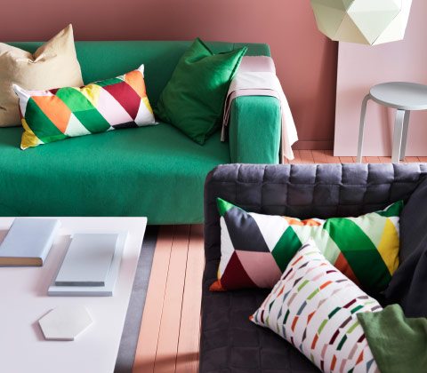 Two sofas with cushions in colourful geometric patterns.