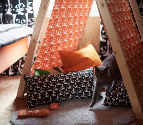 A tent made of wooden posts and a fabric with orange cat face pattern shown together with cushions with black cat face pattern.