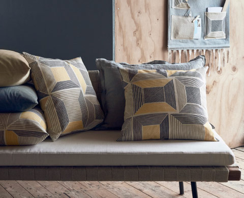 Cushions made of fabric in gray and yellow with a geometric pattern.