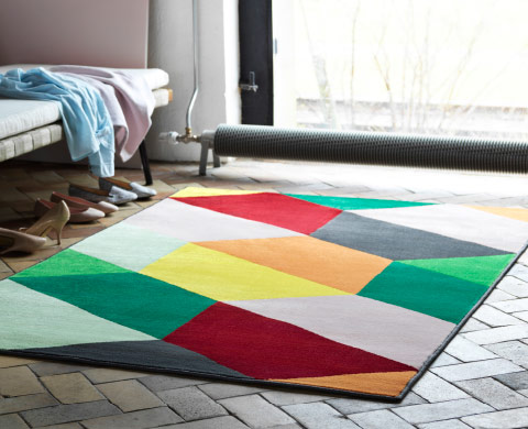 A rug with colourful geometric pattern.