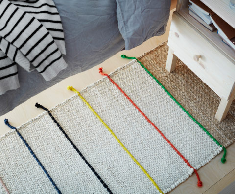 A natural-colored hand-woven jute rug with colored bands.