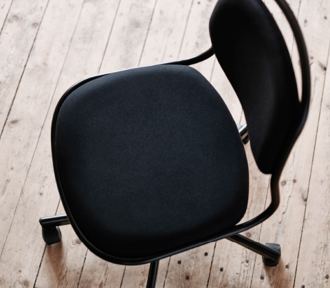 Close-up of a black swivel chair on castors.