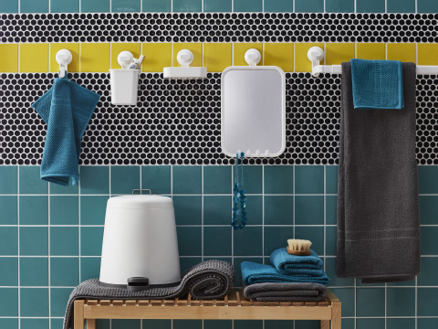 White bathroom accessories attached to a wall with brightly coloured tiles