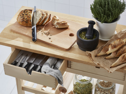 Bread being sliced on a wooden chopping board that's placed on a kitchen utility cart