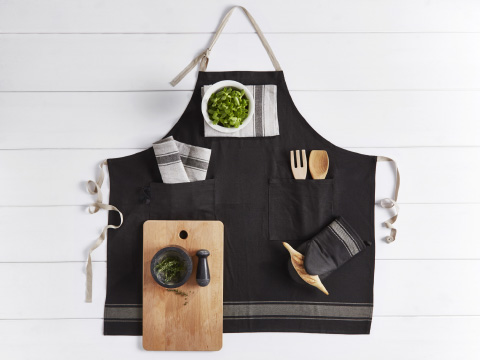 A black and beige apron spread out on a white floor