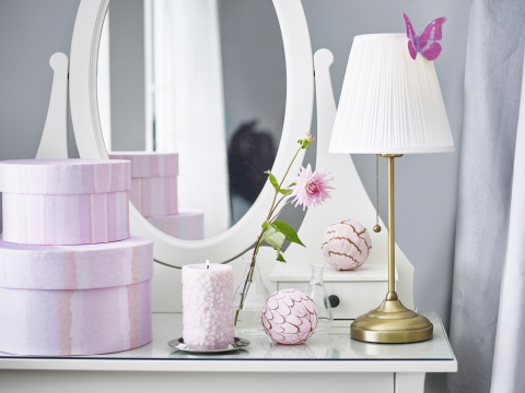 A white dressing table with pink boxes and accessories