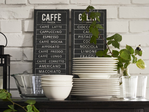 A table with stacks of off-white tableware and two black and white pictures listing types of coffee and ice cream
