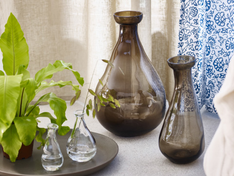 A close-up of two small clear glass vases on a plate in front of two, larger, brown glass vases