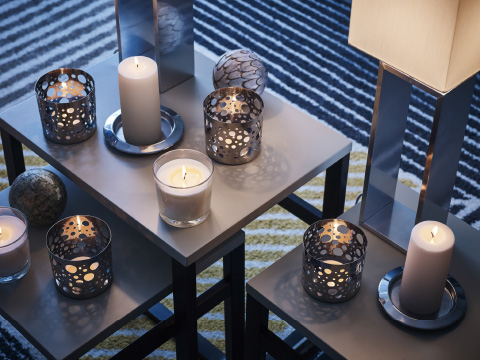 Three small tables filled with tealight holders and candles