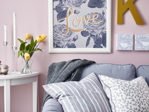Gray and white pictures on a pink wall above a gray sofa