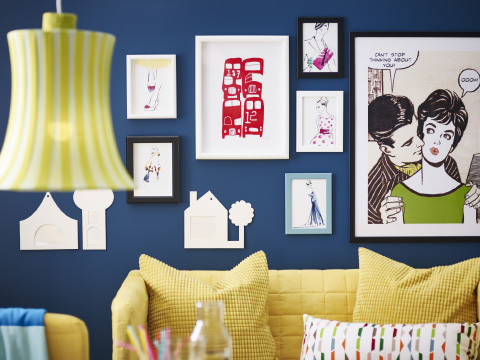 Colourful pictures on a dark blue wall above a yellow sofa
