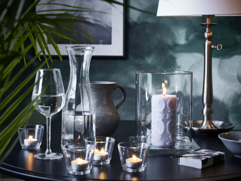 Clear glass tealight holders, a lantern and assorted glassware on a black table