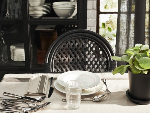 A close-up of a beige and off-white table setting and a black rattan chair