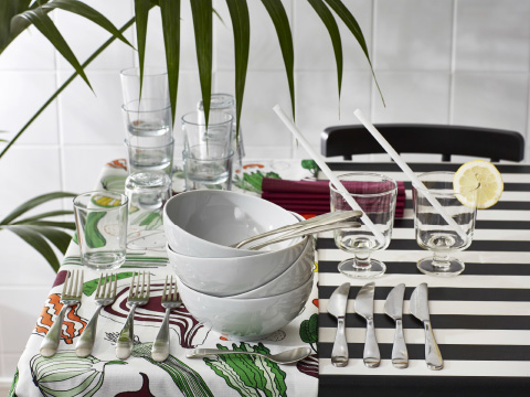 A table setting with a black and white striped tablecloth, a multicoloured table runner and a stack of white bowls