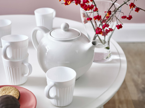 A white teapot and cups on a white table