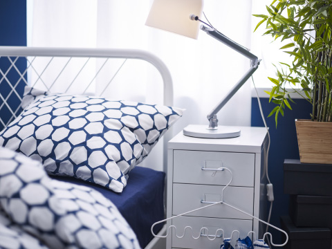 A close-up of a bed with dark blue and white bedlinen and a bedside table with a white work lamp