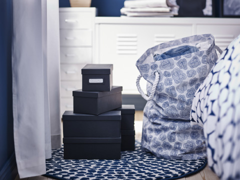 Stacks of black boxes and a blue and white laundry bin on a rug with dark blue dots