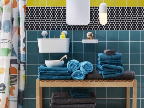 Turquoise and grey towels stacked on a bench in a bathroom with brightly coloured tiles