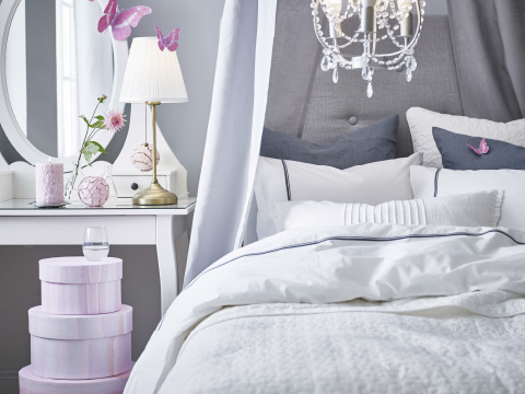 A bed with white and grey bedlinen next to a white dressing table and a stack of pink boxes
