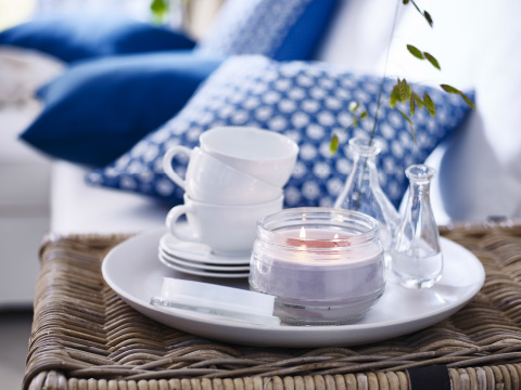 A white plate with a scented candle, a stack of cups and two glass vases with blue and white cushions in the background