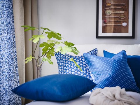 Blue and white cushions in front of a window with blue/white and beige curtains