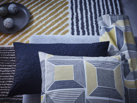 Close-up of a cushion, fabric and a rug with striped and square patterns in yellow, black and white